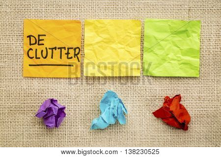 declutter concept - colorful sticky notes against burlap canvas