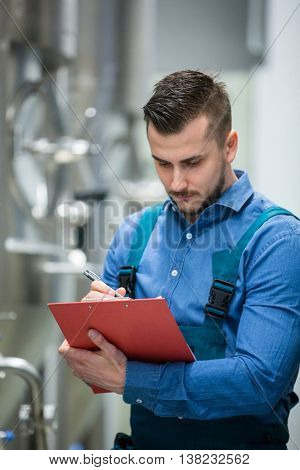 Attentive maintainance worker writing on clipboard at brewery