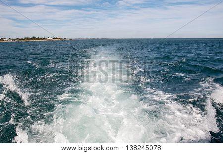 Boat wake in the Indian Ocean waters under a cloudy sky in Rockingham, Western Australia.
