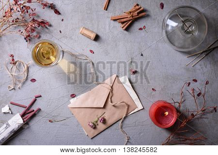 Invitation or love letter, glass of wine, burning candle and aromatic sticks. Valentine's day or Weding day background.