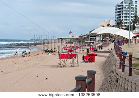 DURBAN SOUTH AFRICA - JULY 09 2016: Locals and tourists on the beach near the Millennium Pier and lighthouse in Umhlanga Rocks