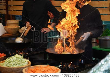 Chefs cooking with flame in a frying pan