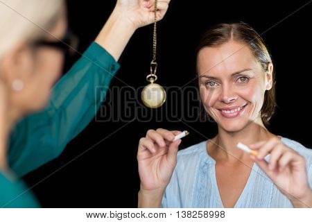 Hypnotherapist holding pendulum by patient against black background