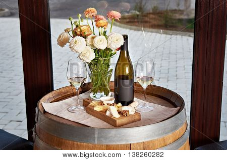 Bottle, Wine Glasses With White Wine And Cheese Appetizer On Barrel
