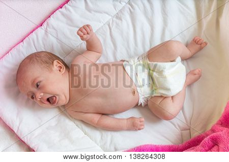 Unpleasant yelling baby girl lying on bed.