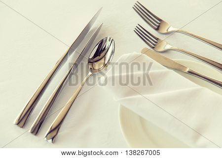 table setting, silverware and eating concept - close up of cutlery set wrapped with napkin and plate on restaurant table