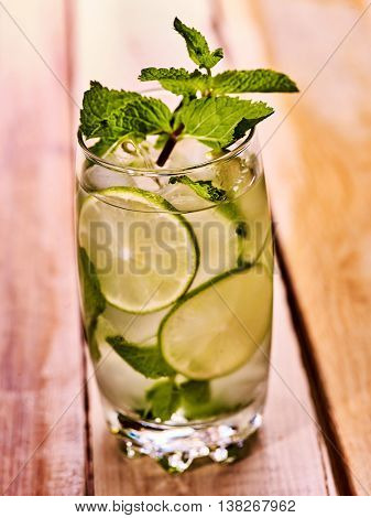 Alcohol drink. On wooden boards is glass with alcohol drink and ice cubes. A drink number hundred forty four cocktail mohito with slice lime and mint leaf. Country life. Outdoor. Close up.