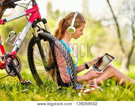 Bikes cycling girl. Girl rides bicycle. Girl wearing headset watch in pc tablet and listing music near bicycle. Cycling on bicycle is good for health. Cyclist looking pc tablet.