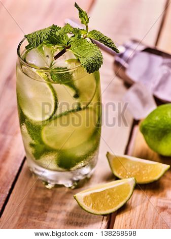 Alcohol drink. On wooden boards is glass with alcohol drink and ice cubes. A drink number hundred thirty eight cocktail mohito and scoop ice on table. Country life. Outdoor. Light background.