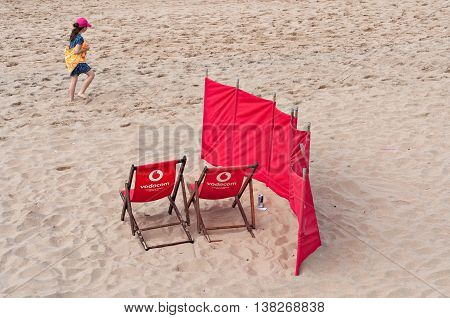 DURBAN SOUTH AFRICA - JULY 09 2016: Young girl walks past two Vodacom beach chairs on the beach in Umhlanga Rocks