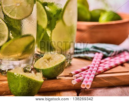 Wooden boards with haf of two glasses with alcohol drink and ice cubes. Mint leaf drink number hundred fifty two cocktail mohito with group straws and lime. Country life. Outdoor. Light background.