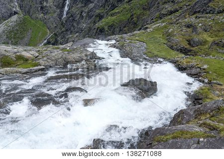 Rushing mountain stream near the Trollstigen road between the mountains, Norway.