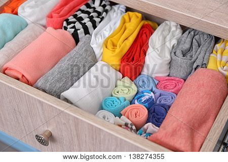 Neatly folded clothes in chest of drawers