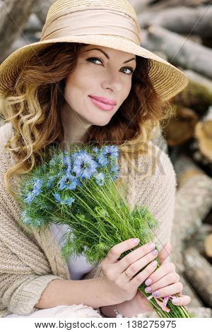 happy young woman with a bouquet of spring nigella