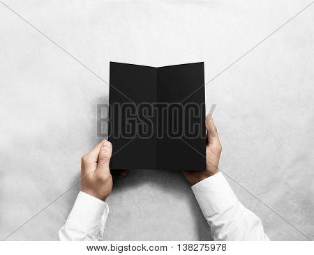Hand opening blank black flyer brochure booklet mockup. Leaflet presentation. Pamphlet mock up holding hand. Man show grey offset paper. Booklet design template. Paper sheet display read first person