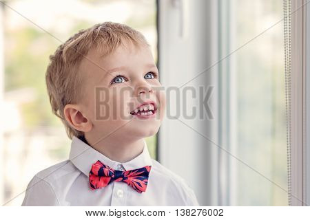 Portrait of a happy little boy with red tie