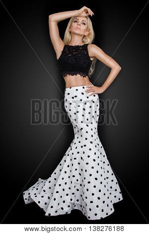 Beautiful blond with long curly hair young woman in the white model black ball gown a polka color with a long train on a black background