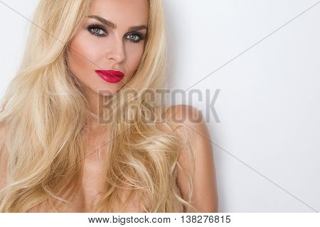 Photo shows a portrait of the beautiful woman in a cute little face makeup with green eyes hairstyle senses in your hair blonde sensually looking upwards on background