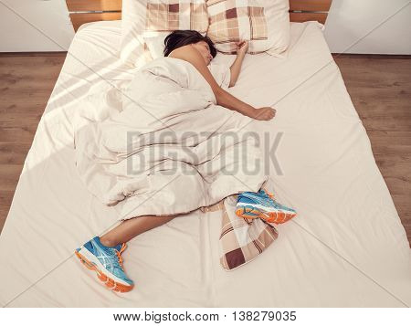 Tired woman sleeps in bed never had taken off the running shoes