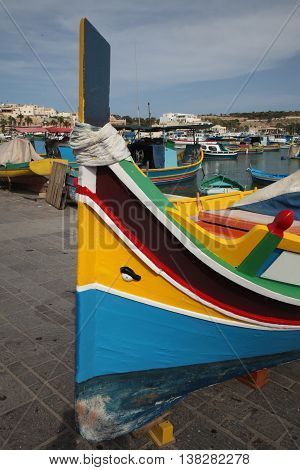 A Maltese traditional fishing boat the Luzzu being repainted in the bright primary colours popular in Malta
