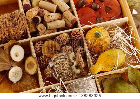 Autumn decoration accessories stored in a wooden compartment.