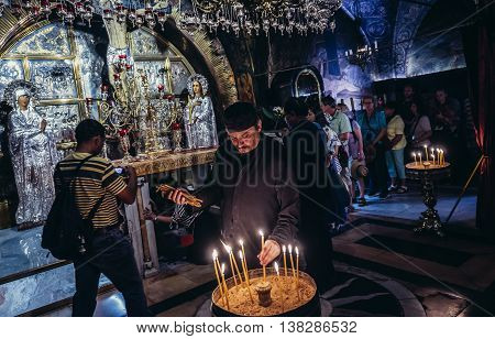 Jerusalem Israel - October 22 2015. Pilgrims and tourists visits altar at the traditional site of Calvary (also called Golgotha) inside the Church of the Holy Sepulchre located in Christian Quarter