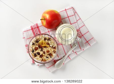 bowl of oat flakes, jug of milk and apple on checkered dishtowel