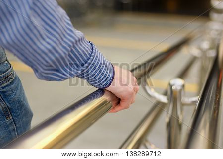 A man down the stairs holding on to the handrail. Hand closeup