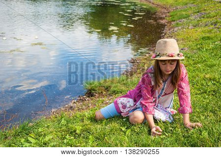 Sad lonely little girl in a hat sitting on the grass on the bank of a pond