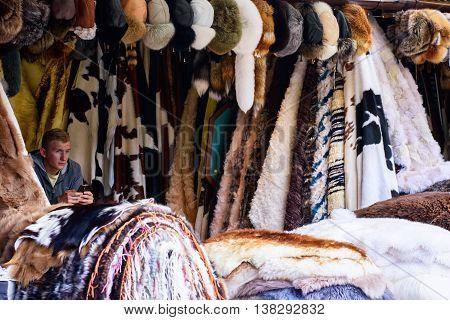 JULY 5, 2016, ZAKOPANE, POLAND - seller of traditonal polish fur on market street.