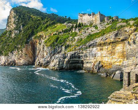 Portovenere, the Byron Cave, beautiful shoreline scenery of Cinque Terre, Ligurian Coast, La Spezia, Italy. On background the Doria Castle that dominates the promontory.