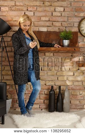Young woman standing by wall at home, using mobilephone.