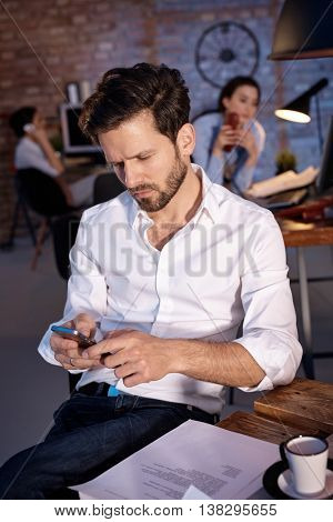 young businessman holding mobilephone in hand, writing text message, sitting at desk.