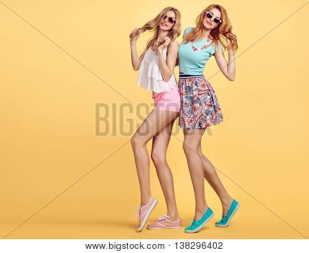 Fashion Hipster woman in Stylish Summer Outfit having fun. Playful sisters friends crazy cheeky emotions.Girl in Trendy Fashion sunglasses, glamour wavy hairstyle posing on yellow.Unusual creative fun