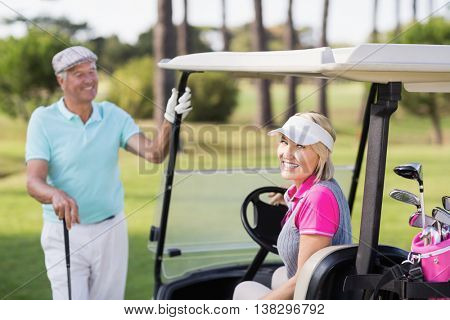 Portrait of smiling mature woman sitting in golf buggy
