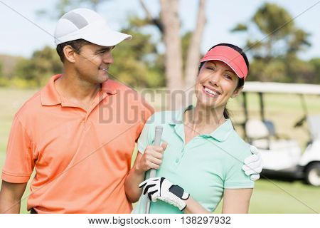 Smart golfer couple with arm around while standing on field