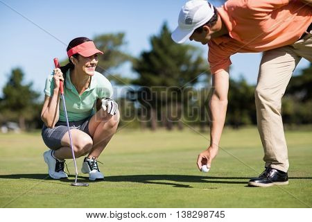 Man removing golf ball from hole by smiling woman crouching on field