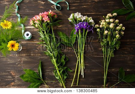 Bright colorful irises, roses, leaves and  alstroemerias on wood table, herberas in vase. From above.