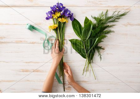 Bright colorful irises and herberas in hands on wood table, green ribbon. From above.