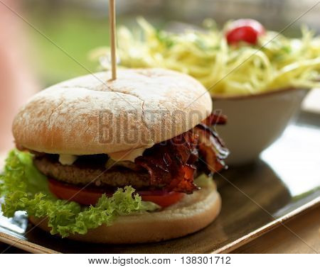 Delicious Burger with Beef Lettuce Grilled Bacon Tomato and Cheese and Bowl with Coleslaw Salad closeup Outdoors. Focus on Foreground