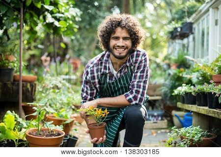 Portrait of smiling male gardener holding potted plant while kneeling outside greenhouse