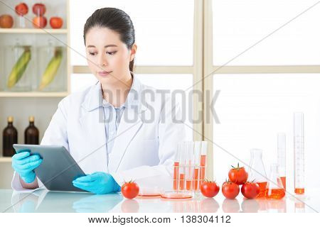 Asian female scientist research for genetic modification food by digital tablet poster