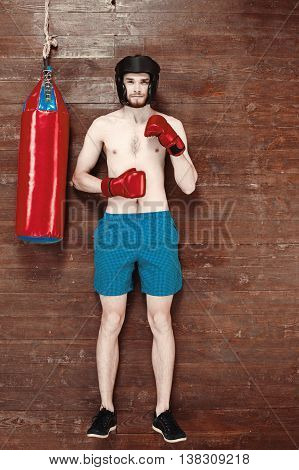 Top view photo of handsome young sportsman on wooden floor. Man with boxing gloves and punching bag