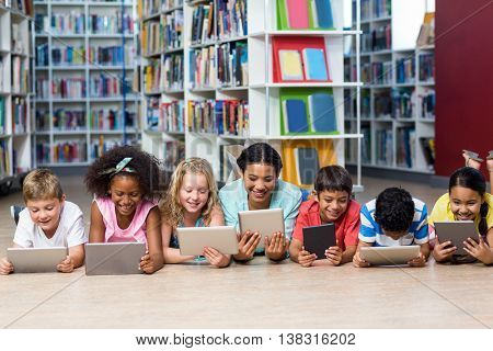 Smiling teacher with students using digital tablet while lying down in library