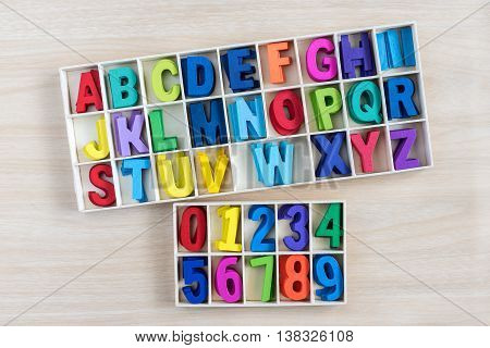 colorful alphabet letters and number in a wooden box with square compartments for teaching kids to read and spell overhead viewful
