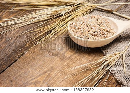 Close-up of wooden spoon filled with wheat bran surrounded by wheat ears on burlap fabric and wooden planks. Dietary supplement to improve digestion. Source of dietary fiber. Shallow depth of field