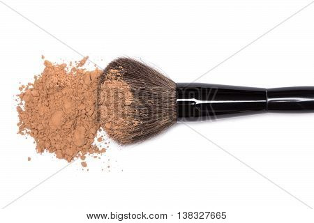 Close-up of large makeup brush with handful of loose cosmetic powder on white background. Top view, shallow depth of field, focus on brush bristle