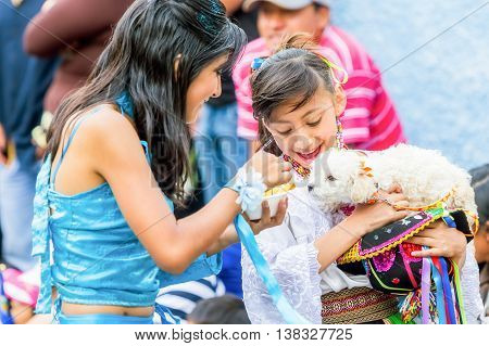 Banos De Agua Santa - 29 November, 2014 : Two Youth Girls Dressed In Ecuadorian Folk Costumes Feeding A Puppy On The Street In Banos De Agua Santa