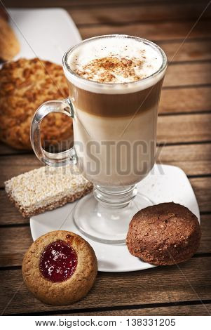 Capuchino coffe and cookies in a table