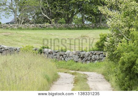 Dirt road through field diverted by New England stone wall